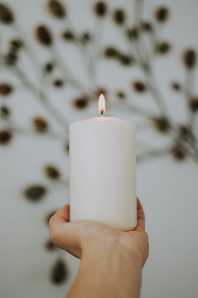 photo-of-hand-holding-lit-white-pillar-candle-1721096